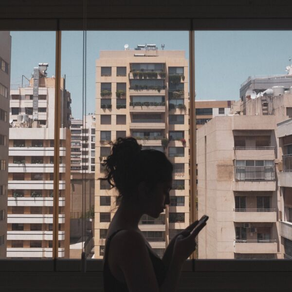 A silhouetted woman standing in front of a large window looking at her phone. Through the window you can see high rise housing blocks.