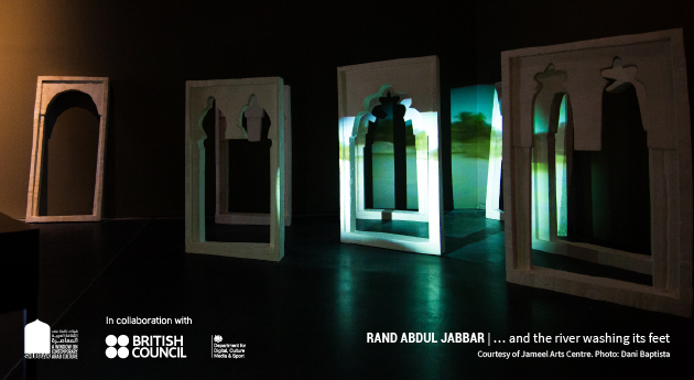 A picture of an exhibition by Rand Abdul Jabbar. A darkly lit room displays freestanding windows from the Minaret of 'Anah