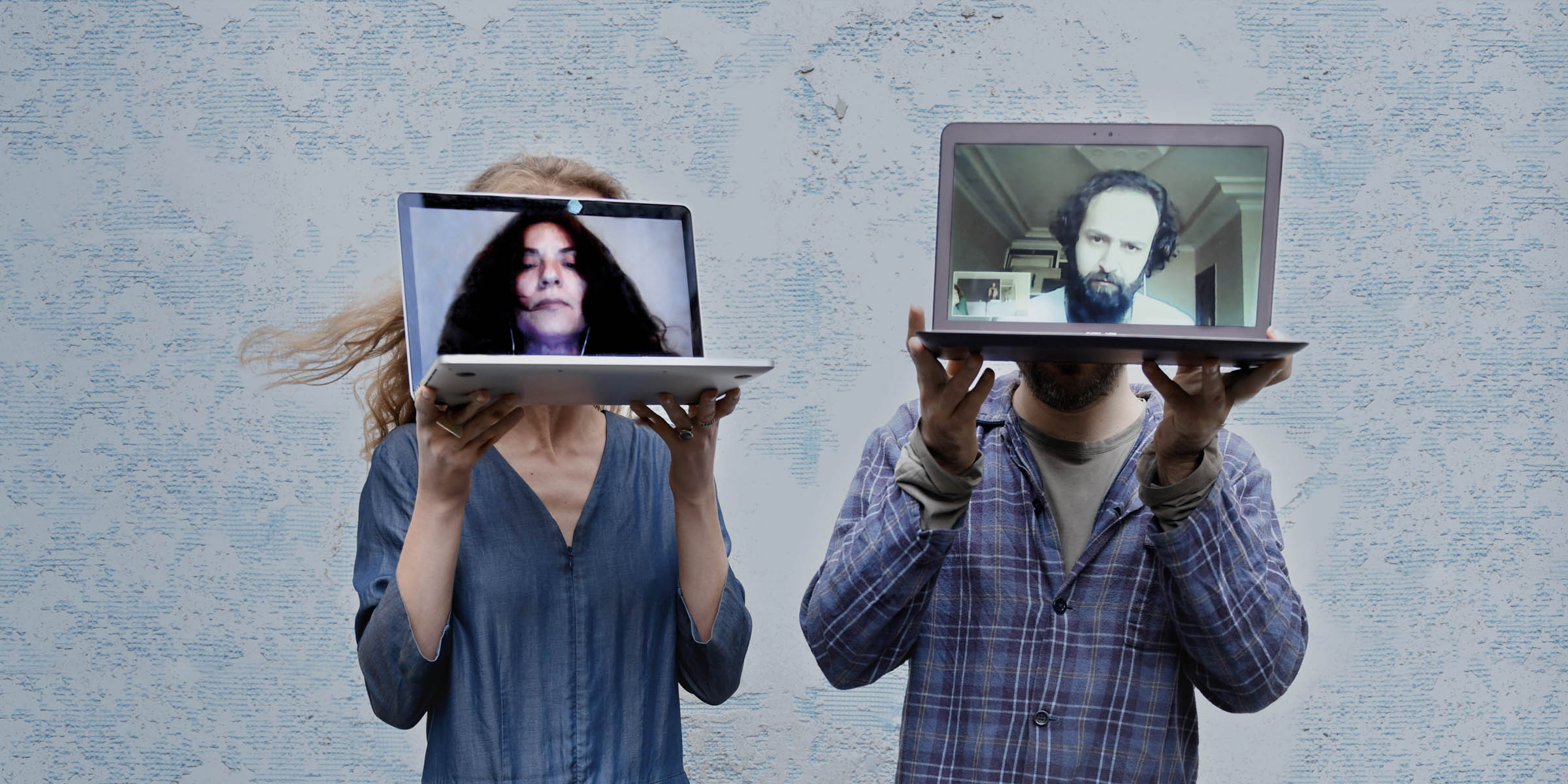 Couple stand with laptops obscuring their faces