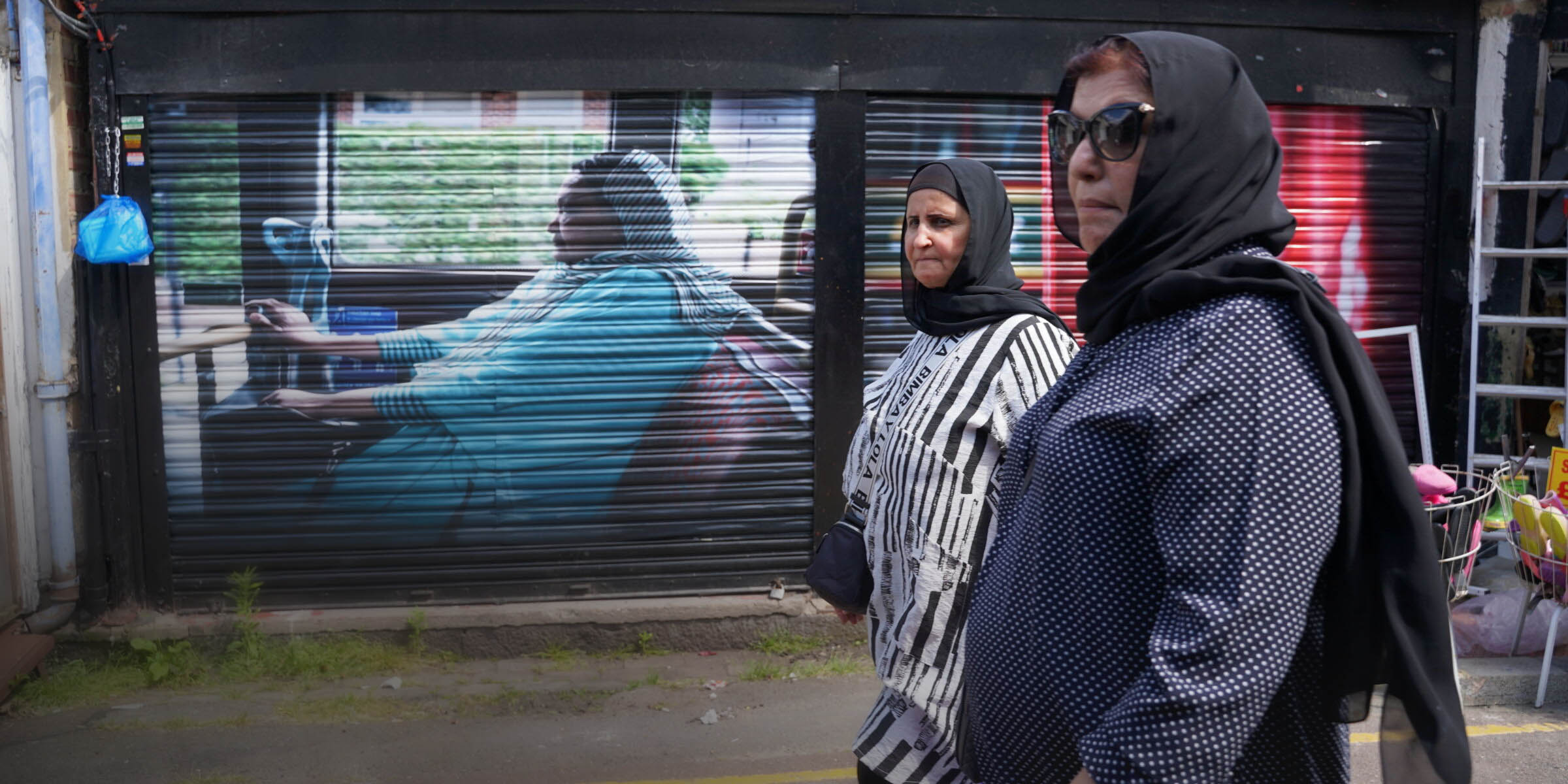 Two women pass in front of a mural on shop shutters