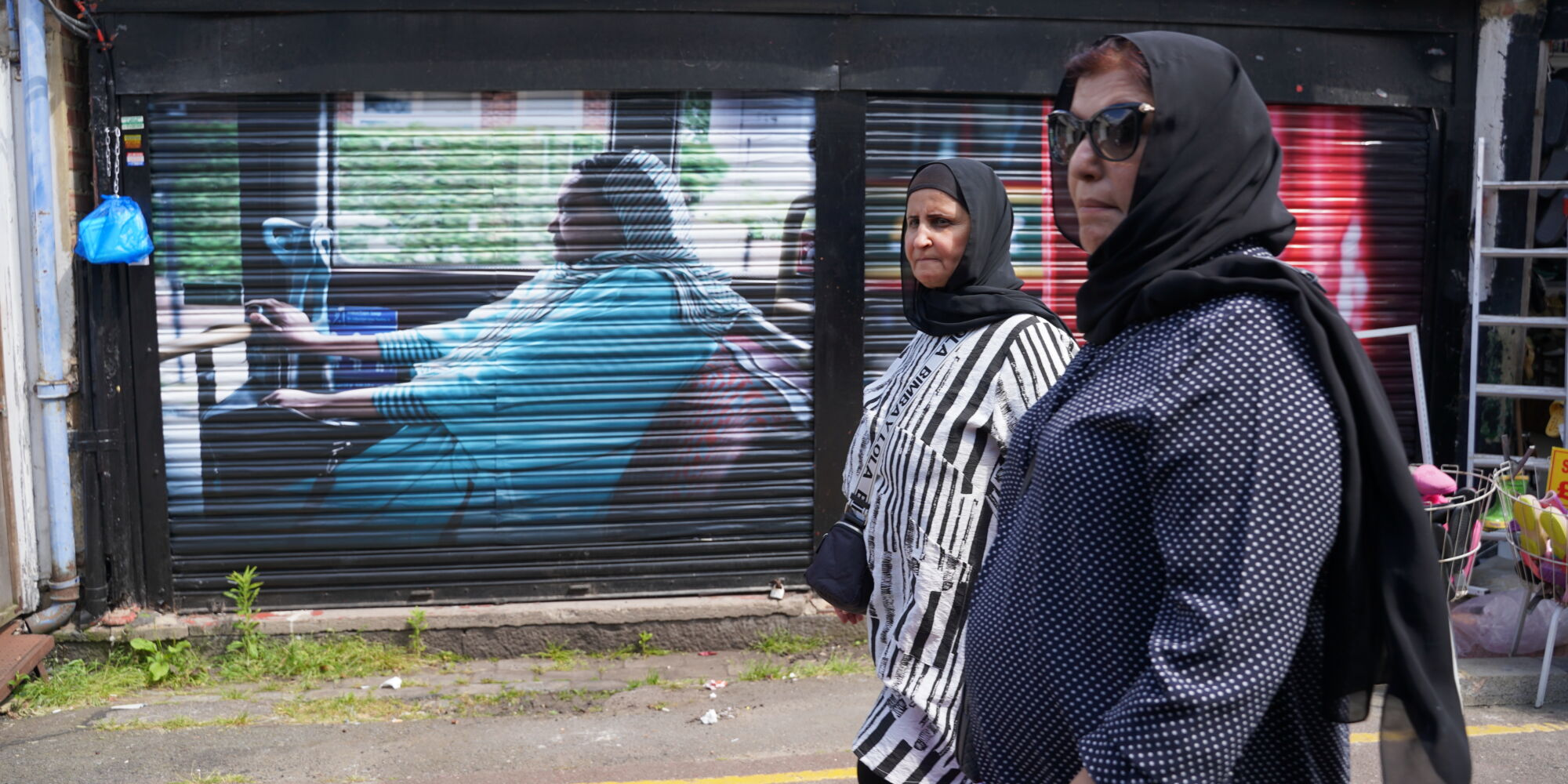 Two women walking past a large-scale portrait of a woman riding on a bus pasted on a market stall shutter in Shepherd's Bush Market