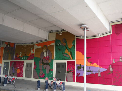 A brightly coloured mural situated on the wall of an underpass in North Kensington. It depicts creatures settling, leaving and searching for new homes under the watchful eyes of an ominous figure.