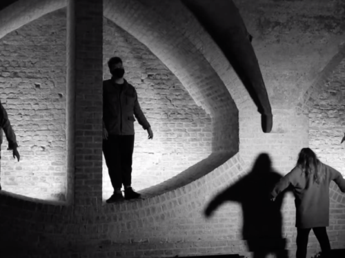 Figures silhouetted against dramatic brickwork.