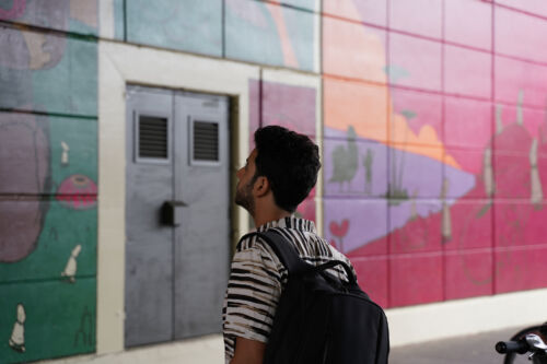 Man stands in front of a colourful mural