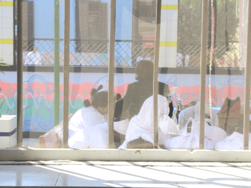 An image of seated women see through a barred window