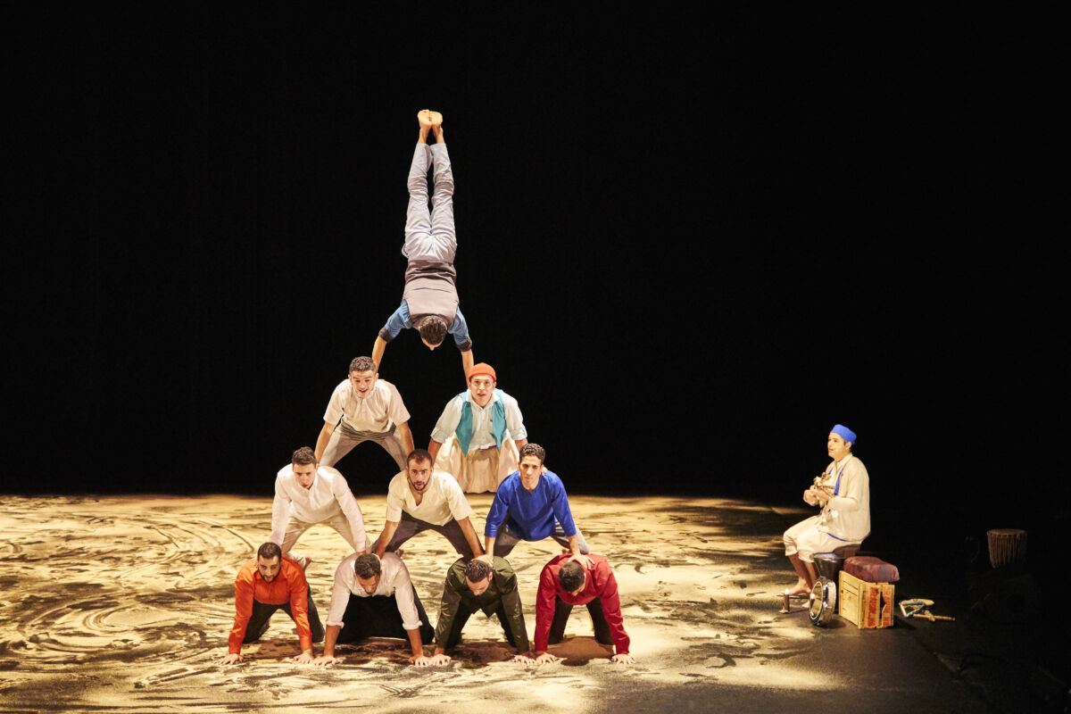 A company of acrobats creating a human pyramid topped off by a circus artist balancing in a handstand.