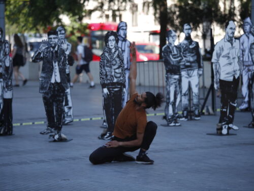 A male dancer wearing a brown short sleeved top and black trousers, kneeling with one arm stretched into the air. He is outside and surrounded by large cutouts of drawings of people.