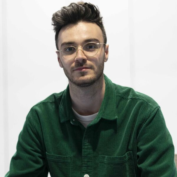 A picture of a white male with brown hair wearing glasses and a green shirt.