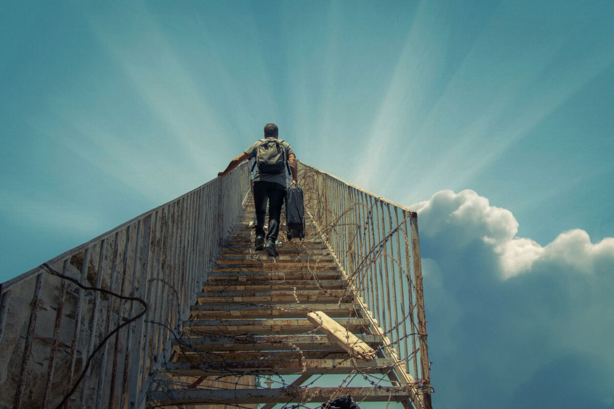 man walks up a staircase into the clouds