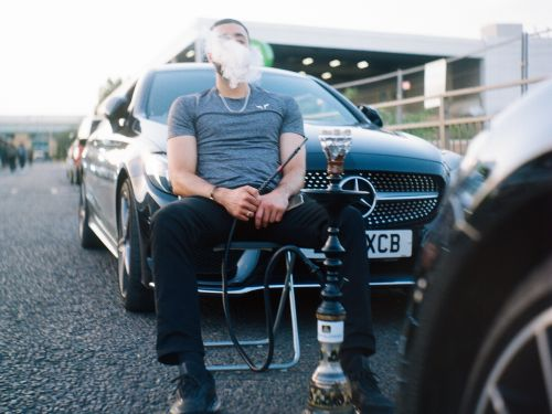 A man sitting in front of a car smoking a shisha pipe