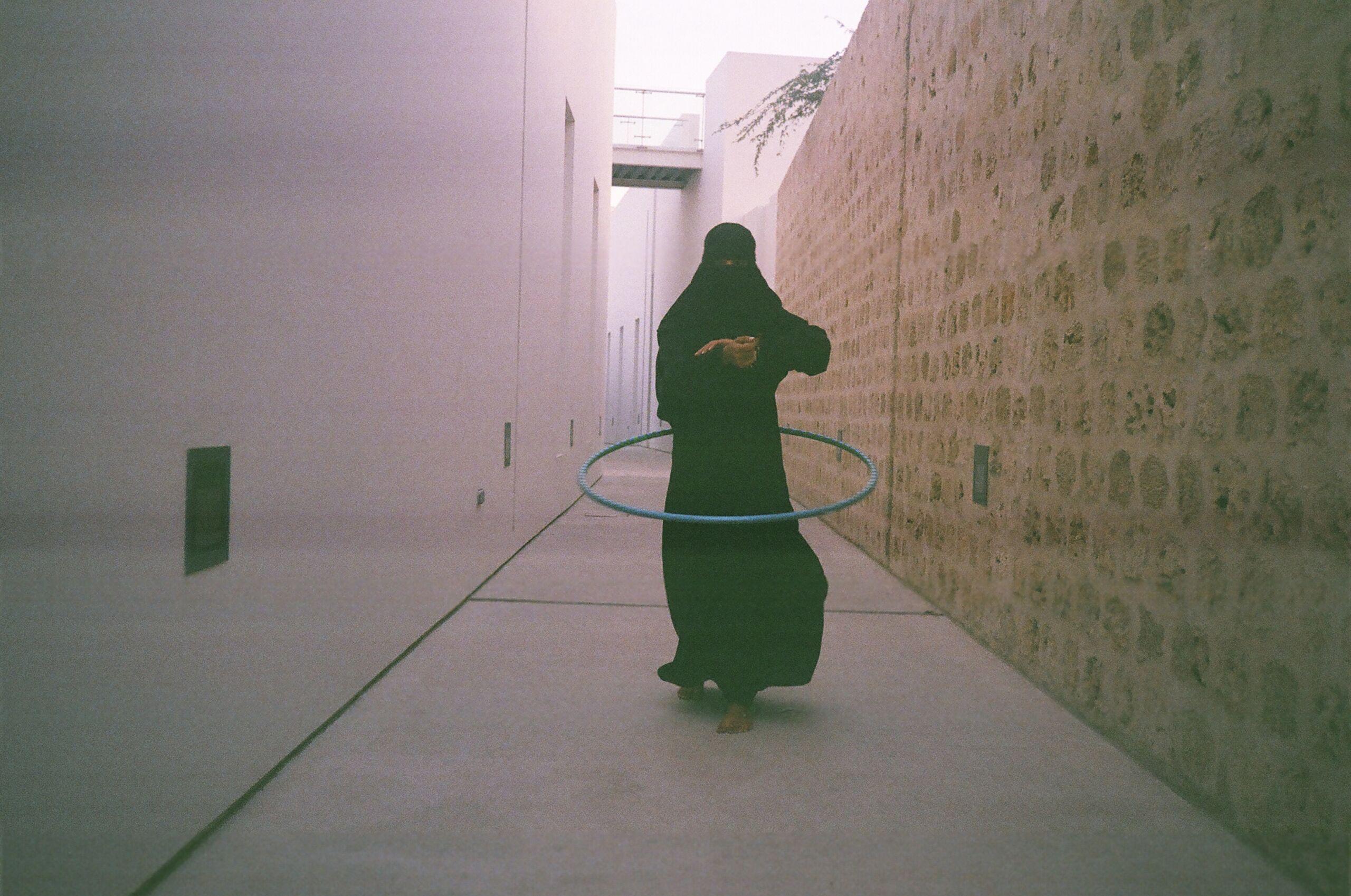 A woman hula hooping in a narrow street
