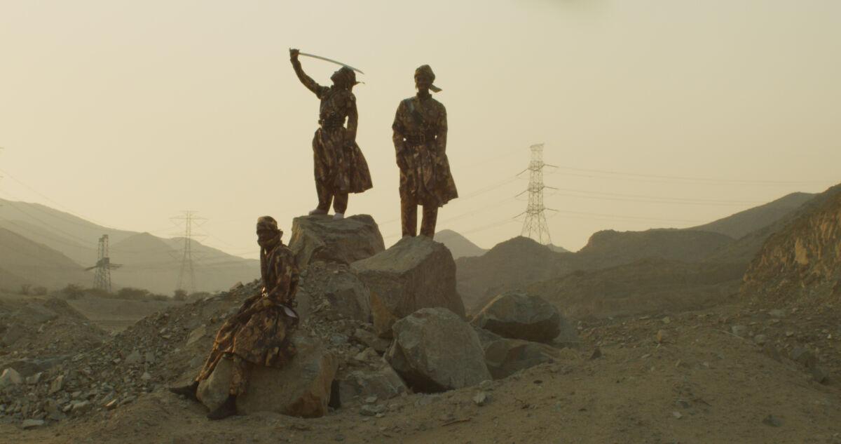 figures on a mound raise a sabre
