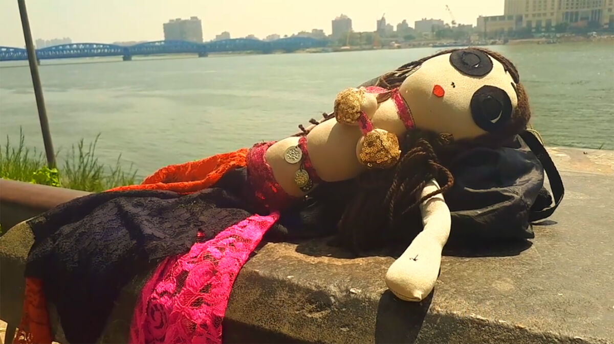 Handmade doll on riverfront