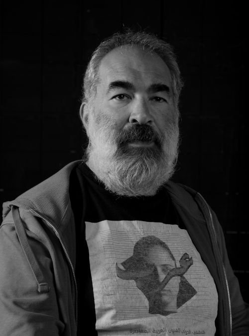 Portrait of Mohamed Alrashi. He has a grey beard and is wearing t-shirt and hoodie