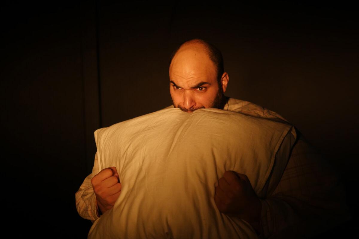 man biting a pillow