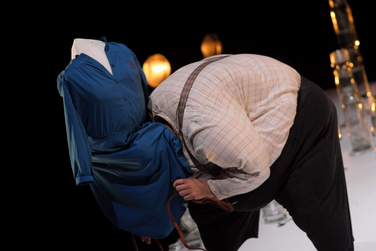 man with his head under a dressmakers mannequin