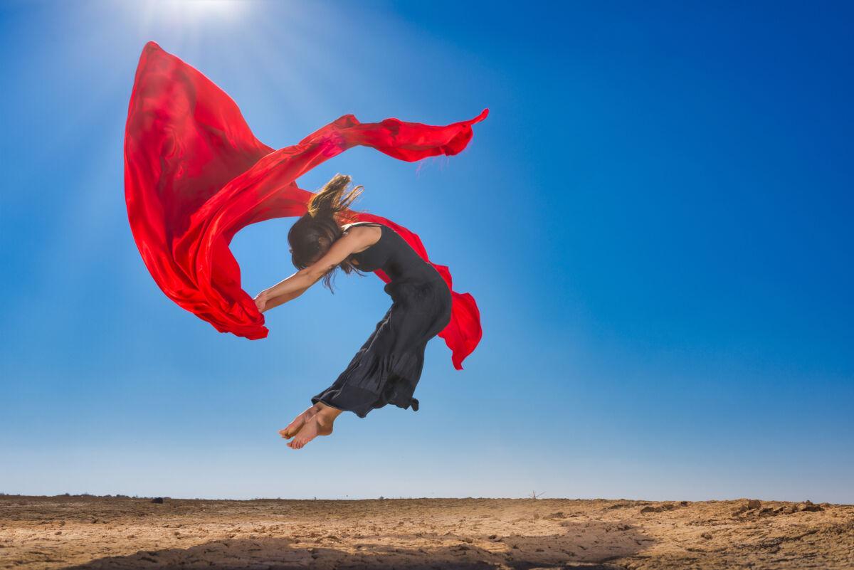 dancer leaps against a desert background