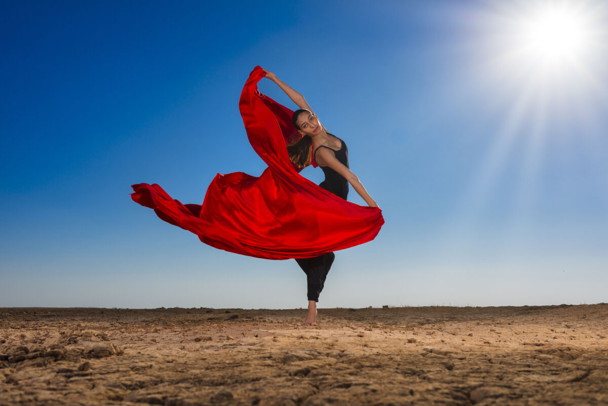 dancer and bright fabric against a desert background