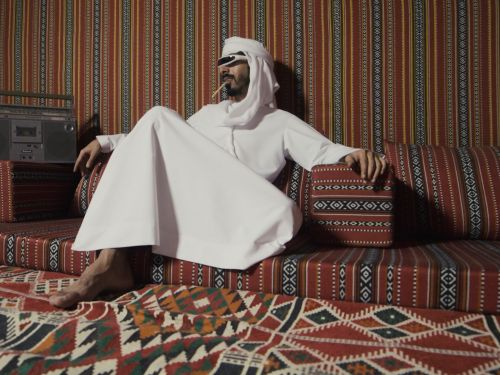 A man dressed in white relaxing on low, patterned cushions