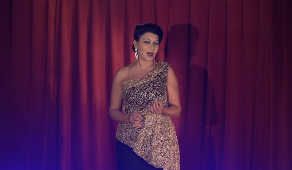 Performer in front of a red curtain