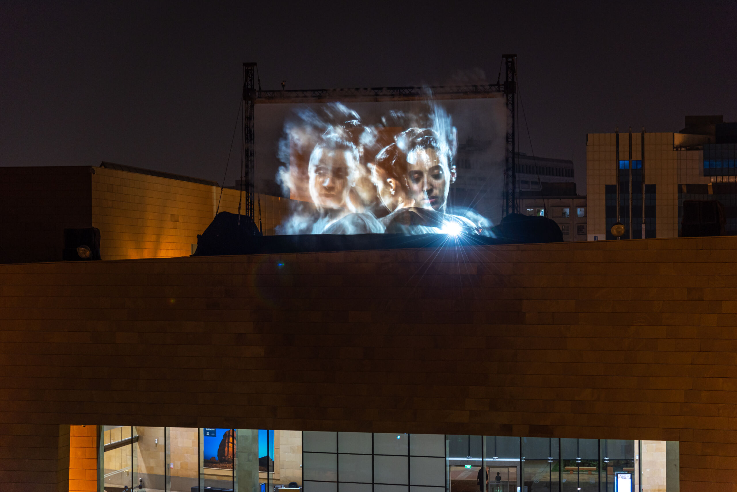figures projected onto a building facade