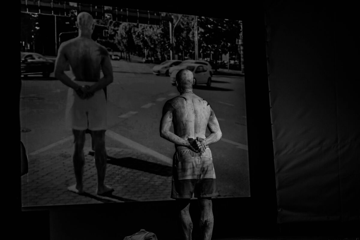 dancer stands in front of a projected image