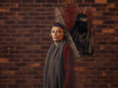 Woman stands against Niqabi Ninja artwork