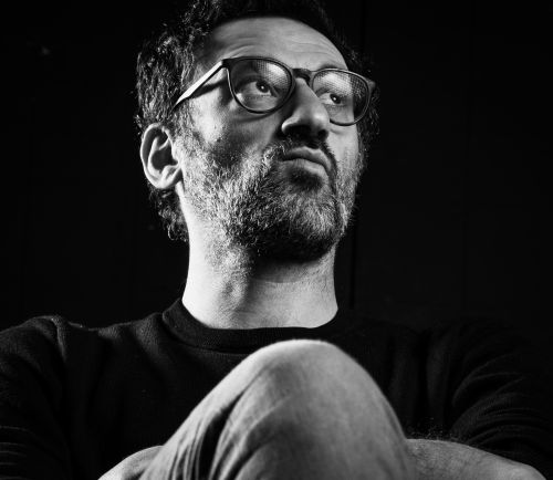 Portait of Omar Elerian. He has a short beard and is wearing glasses.