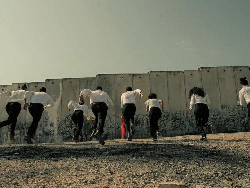 Line of dancers run towards a wall
