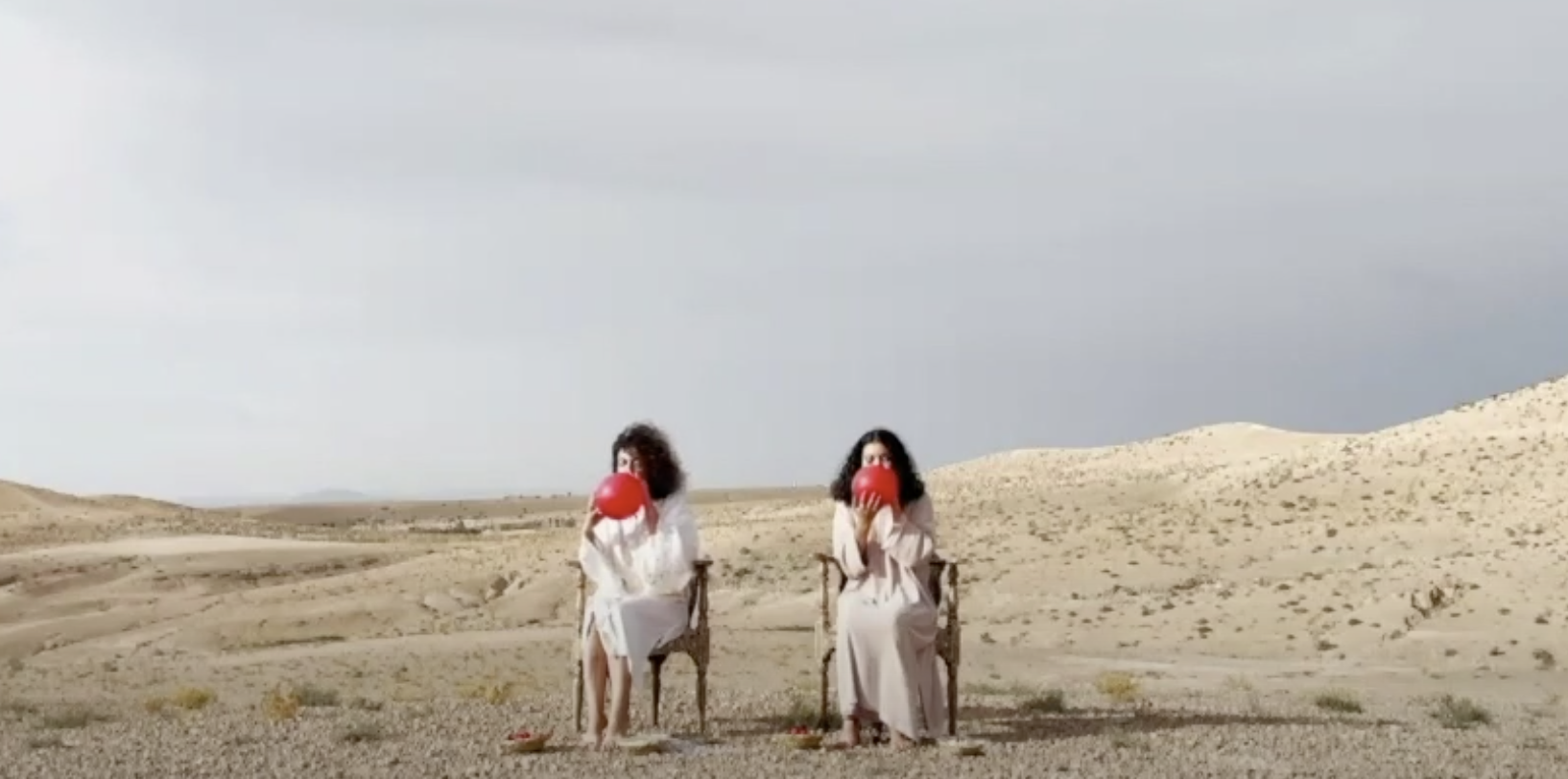 Two women sitting on chairs in the desert