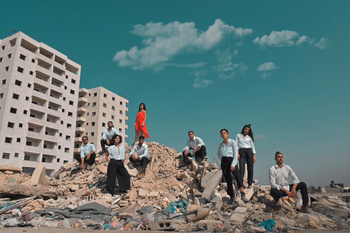Dancers pose on top of building wreckage