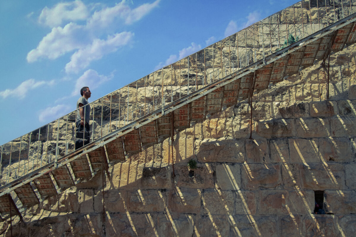 man walks up a staircase against a stone wall