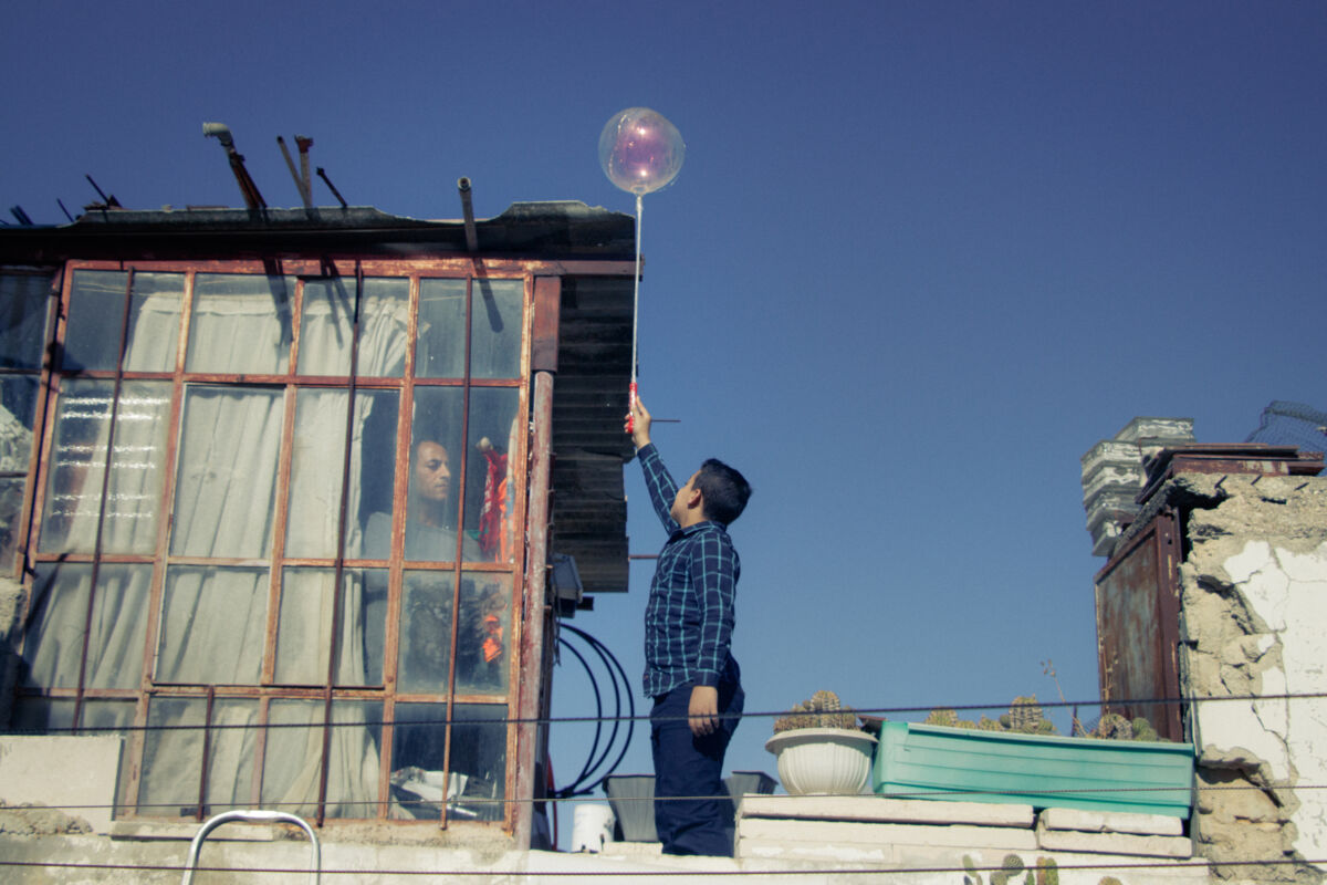 boy holding a balloon on a rooftop