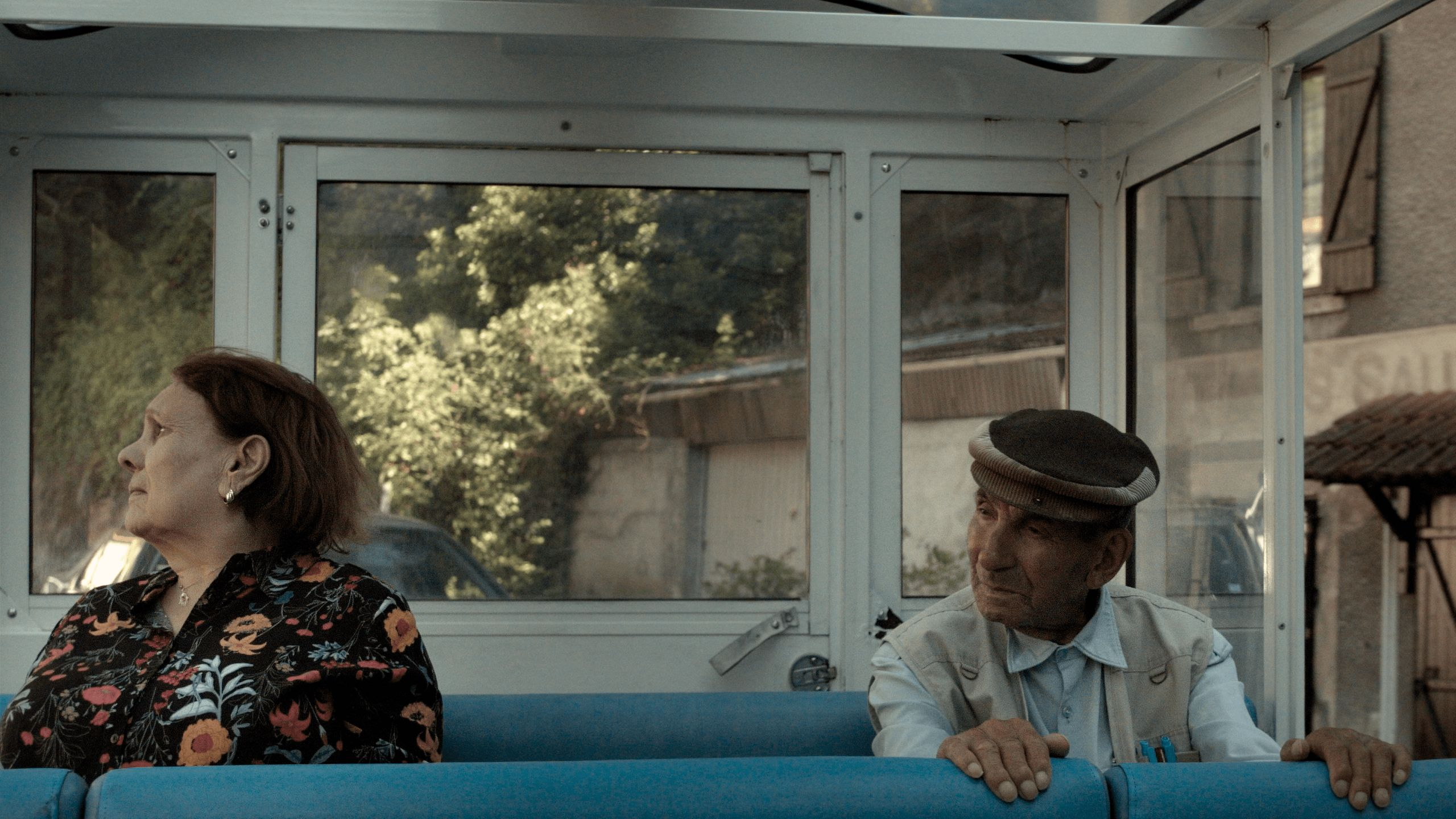 An elderly man and woman sitting on a bus