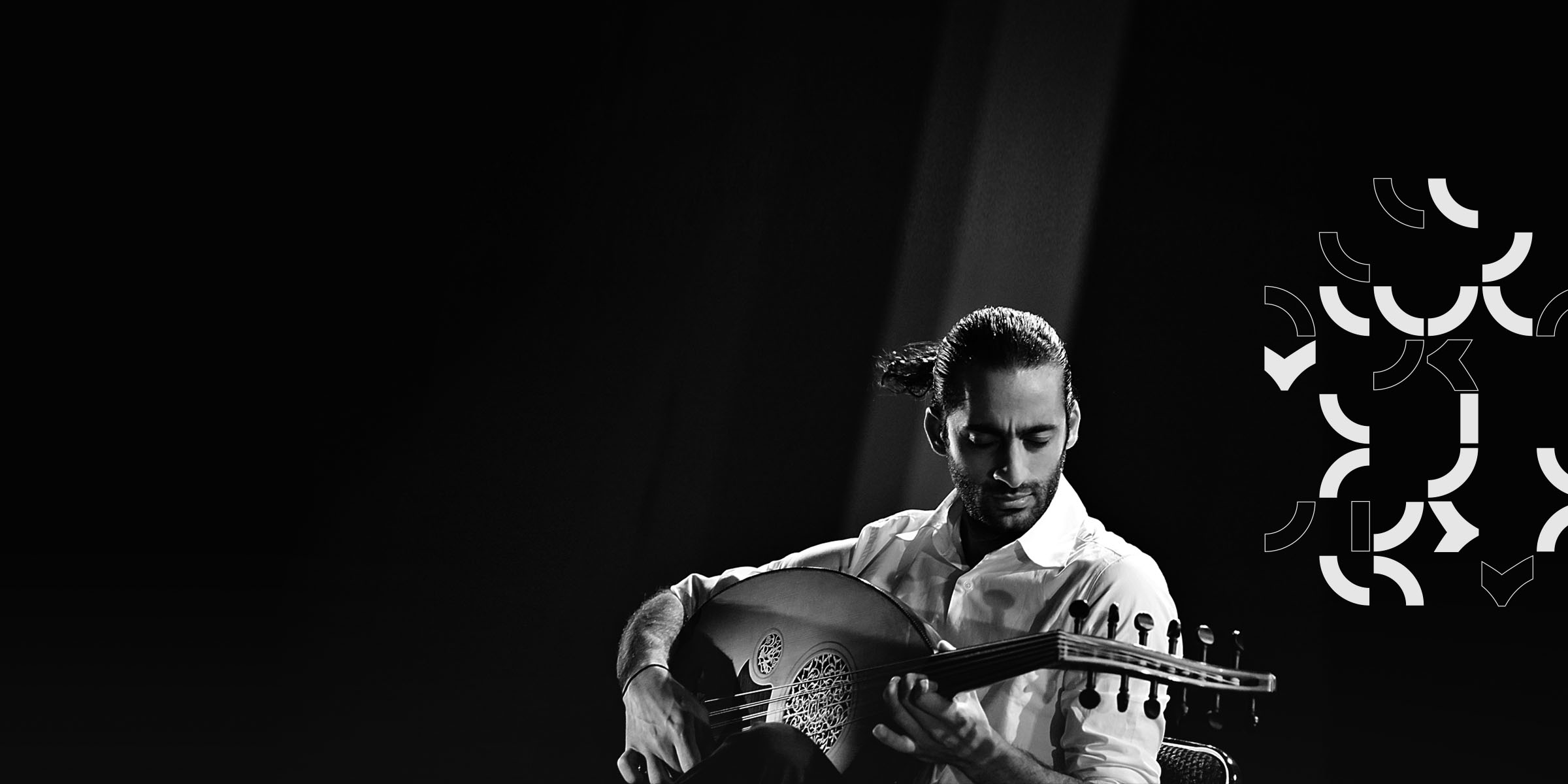 Spotlit performer playing an oud