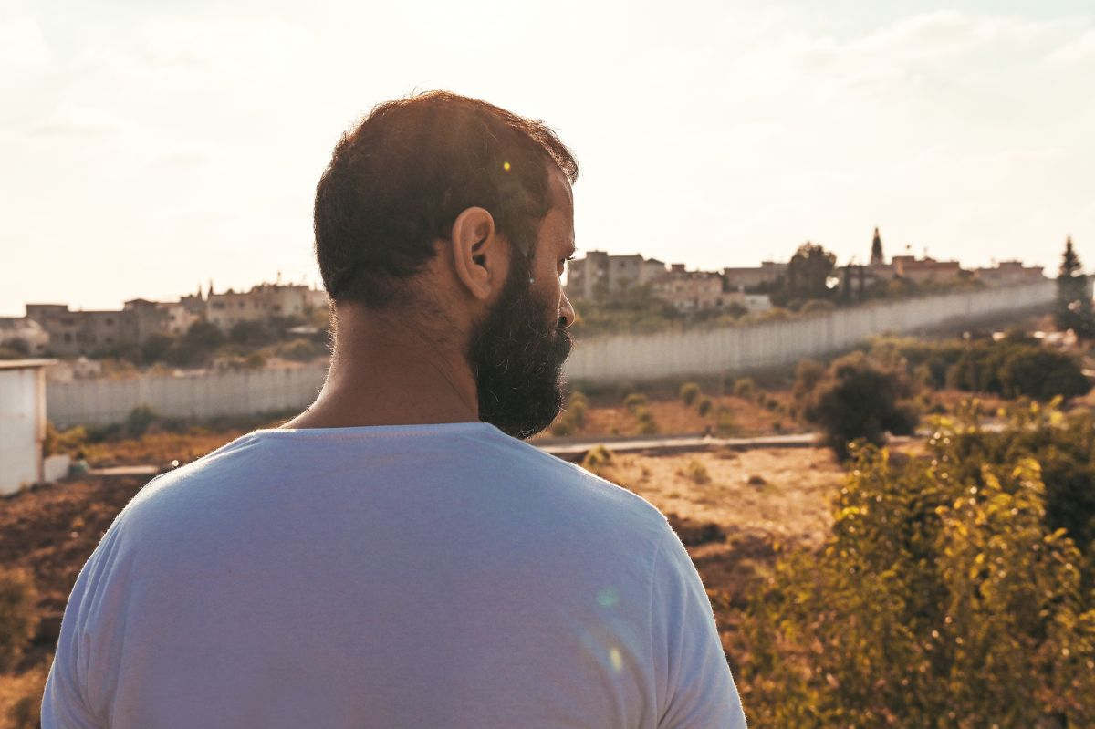 A man with brown hair and a beard wearing a white t-shirt with his back to the camera looking at the dividing wall in Jerusalem