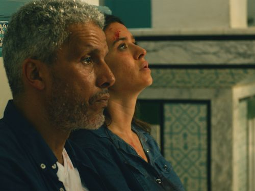 A grey haired man and a dark haired woman with a cut above her eye sitting side by side