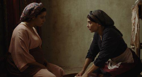 Two women wearing headscarves in conversation in a darkened room
