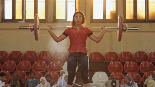 A female weight lifter wearing a chalk covered red top and black knee length leggins