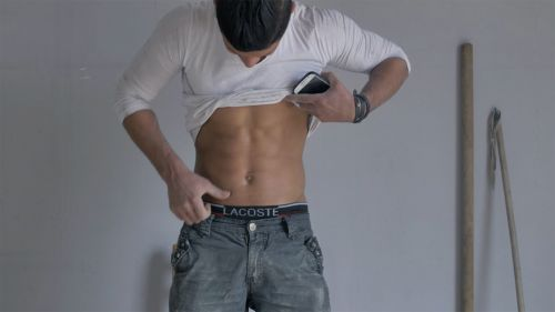 A man wearing Lacoste underpants and underneath a pair of jeans lifting his t-shirt to reveal his torso