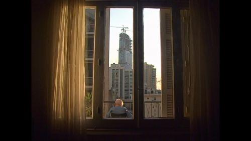 An elderly man sitting on a chair on a balcony seen through large, full length windows framed by curtains