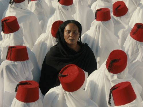 A black woman dressed in black surrounding by people in white robe and red fezes