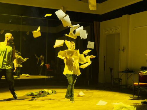 A image of a woman in a studio throwning an armful of paper into the air