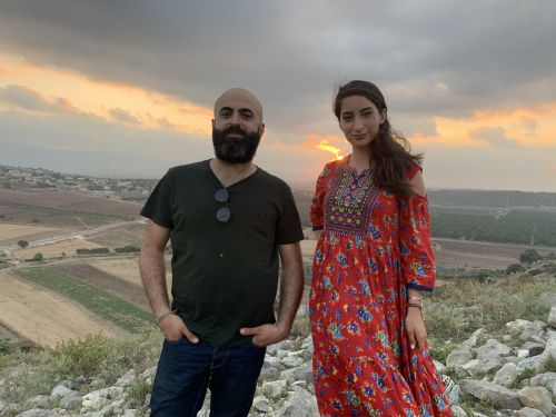 Portrait of Saied Silbak and Nour Darwish standing on a hill with a rural landscape in the background