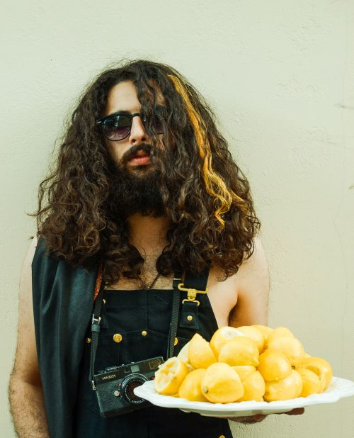 Beardy long-haired man in dungarees holds plate of lemons