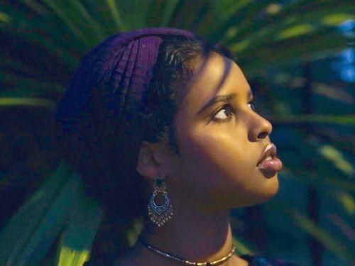 A side profile of a woman wearing a purple head wrap