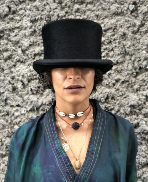 A woman wearing a top hat pulled down over her eyes.