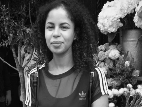 A black and white portrait of a woman wearing an Adidas t-shirt