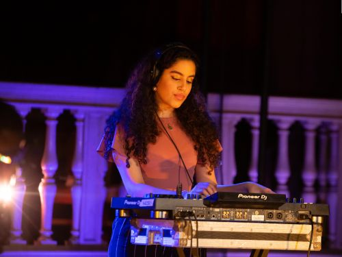 A picture of a woman wearing a short sleeved t-shirt on a balcony wearing headphones and stood at a mixing desk