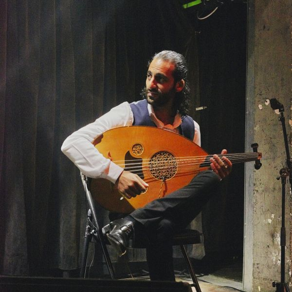 A musician sitting on a stool holding an oud